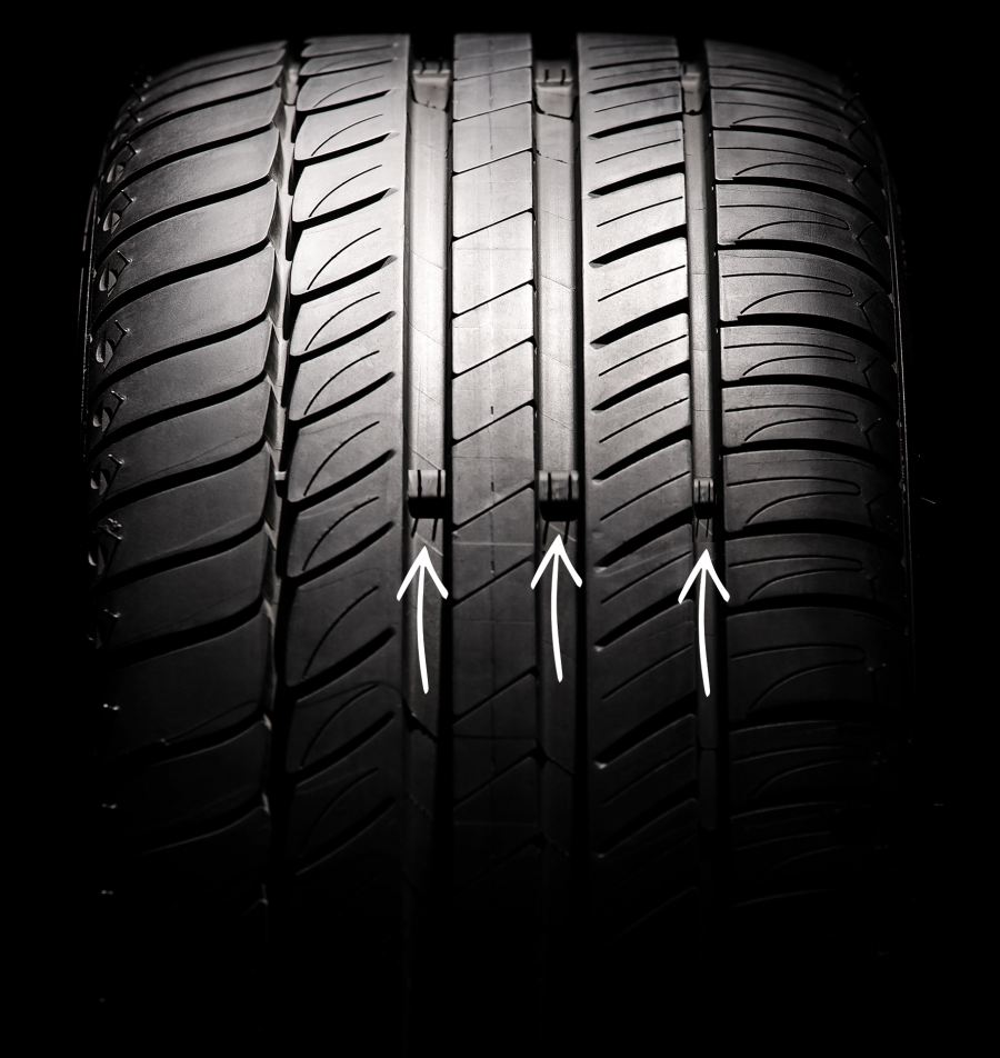 Arrows point to Tread Wear Indicator, which enable motorists to visually compare their tyre tread depth to the legal minimum tread of 1 mm.