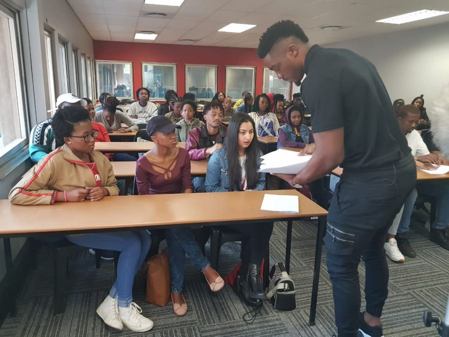 "Tino Chinyani lecturing a group of ""befuddled university students"""