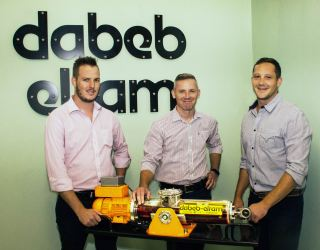 Stuart Palmer (Production Manager, Dabeb-Engineering), Freddie Kühn (Regional Manager, Hytec) and Nathan Pearce (Executive Director, Dabeb-Engineering) with a model of the DEA range of electro-hydraulic actuators.