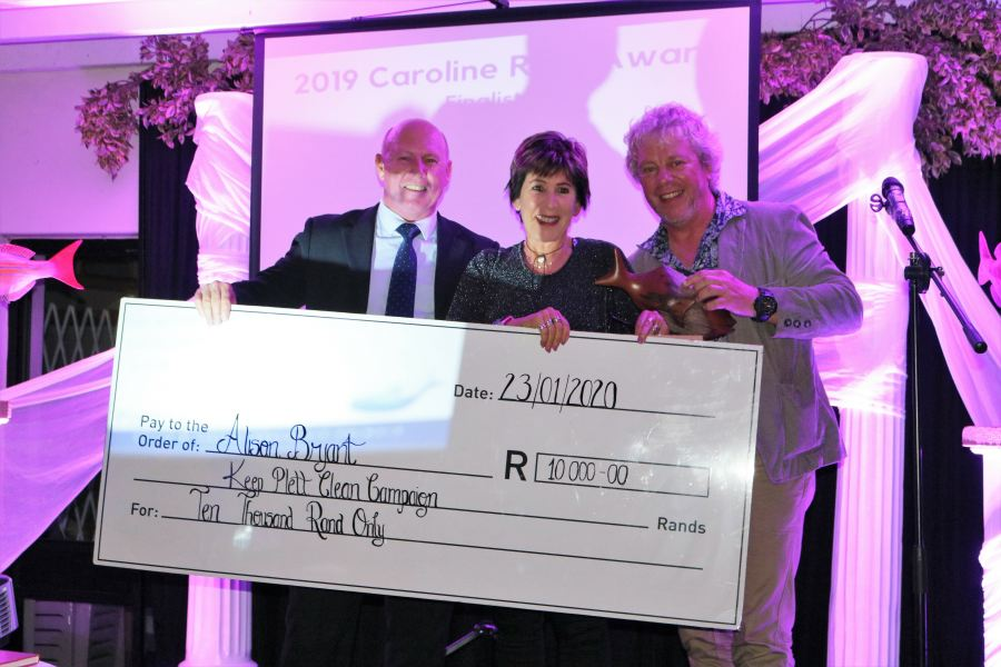 Douw Steyn (left) and John Kieser (right) of Plastics|SA award the cash cheque and trophy to Alison Bryant (middle) of the Keep Plett Clean Campaign